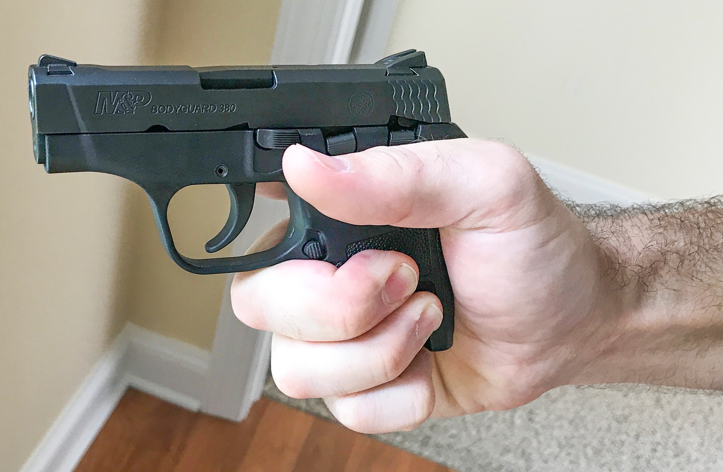 Support side view of one-handed grip on small pistol by large right-handed shooter